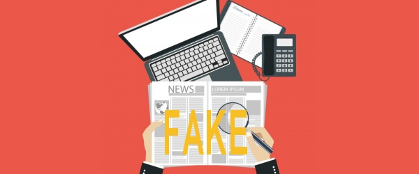 scrivania con pc e quotidianocon scritto FAKE NEWS