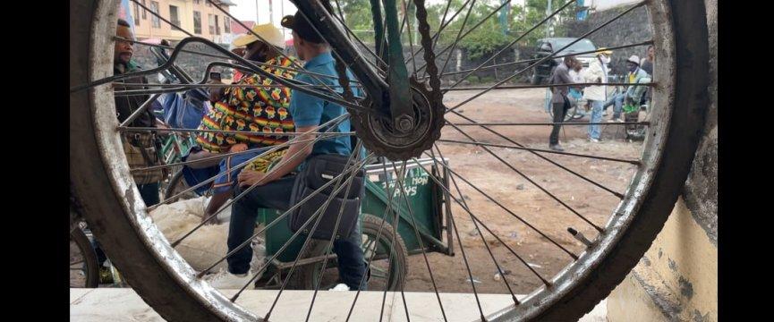 alcune persone disabili su carrozzine di fortuna viste dal fotografo attraverso i raggi di una ruota