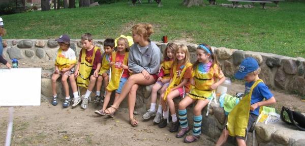 6599c127b3 bambini con casacche gialle per identificarli seduti su un muretto, accanto  a un prato,