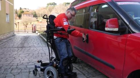 Gianni vicino alla sua auto sulla carrozzina verticalizzante ergo stand