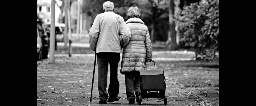 coppia di anziani di spalle mentre camminano su un marciapiede