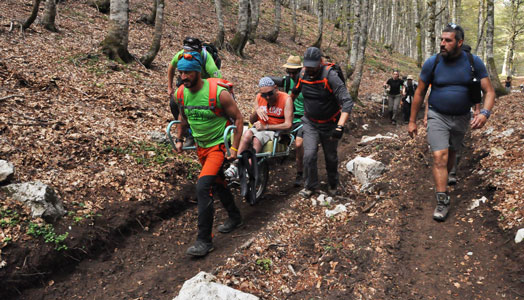 guide accompagnano disabile in montagna su una joelette