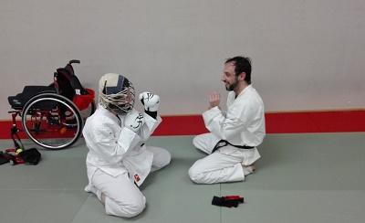 donna seduta sul pavimento in tenuta da combattimento giapponese pronta a combattere contro un uomo. Nello sfondo a sinistra una carrozzina