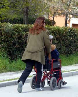assistenza: una donna spinge una persona su sedia a rotelle
