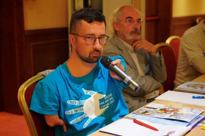 un partecipante con disabilità agli arti superiori interviene alla tavola rotonda
