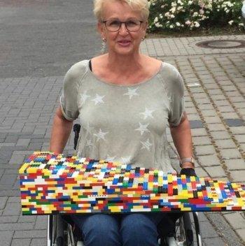 Rita Ebel sulla carrozzina con una rampa di lego in mano