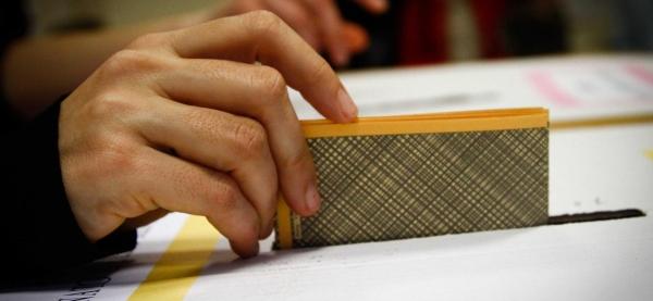 dettaglio di una mano che inserisce la scheda elettorale nell'urna