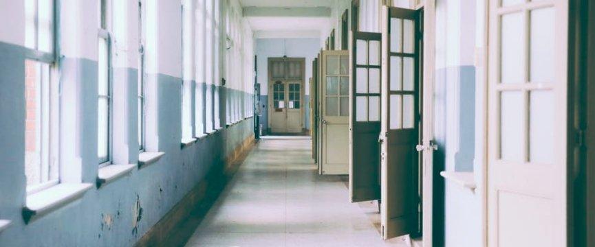 un corridoio scolastico vuoto con le porte aperte delle aule